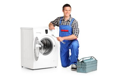 A washing machine being repaired by a man in blue overalls